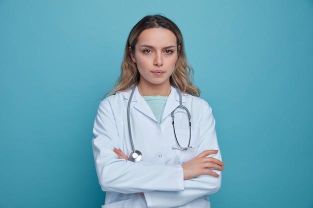 Jovem médica séria, vestindo bata médica e estetoscópio ao redor do pescoço, em pé com postura fechada