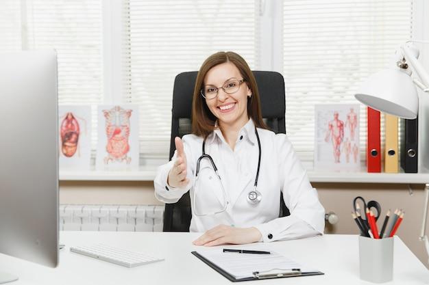 Jovem médica sorridente em pé com a mão estendida para saudação, sentada à mesa com documentos médicos em um consultório em hospital