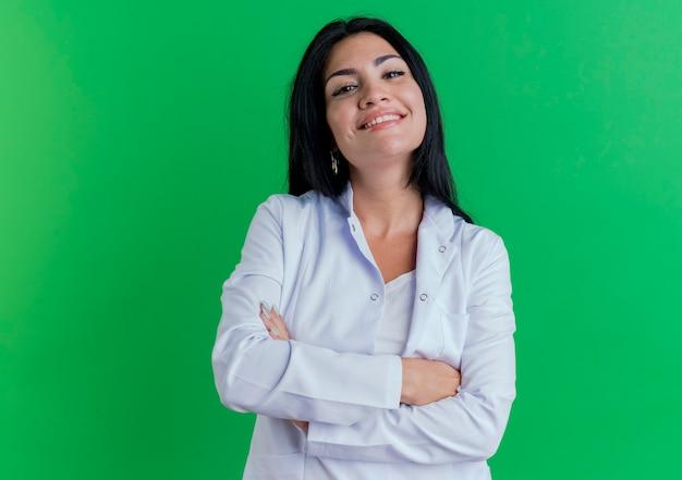 Jovem médica sorridente usando manto médico e parecendo em pé com a postura fechada