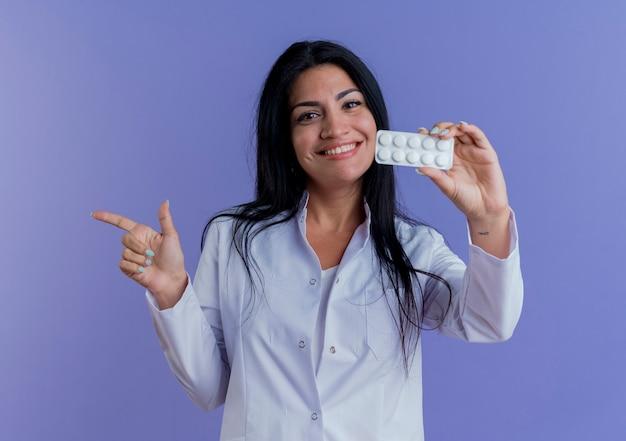 Jovem médica sorridente usando manto médico, mostrando a embalagem de comprimidos médicos, olhando apontando para o lado