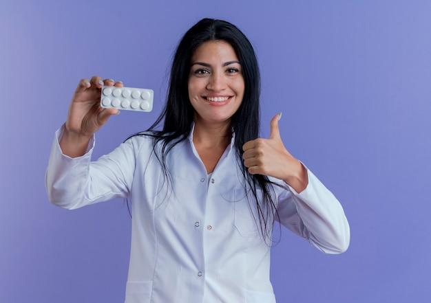 Jovem médica sorridente usando manto médico mostrando pacote de comprimidos médicos, olhando aparecendo o polegar
