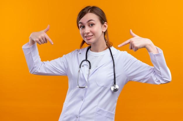 Jovem médica sorridente, vestindo bata médica e estetoscópio, apontando para ela mesma na parede laranja isolada