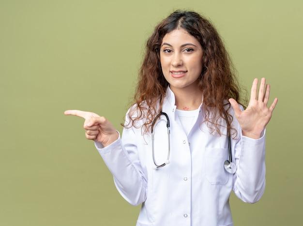 Jovem médica sorridente, vestindo bata médica e estetoscópio, olhando para a frente, mostrando cinco com a mão e apontando para o lado isolado na parede verde oliva