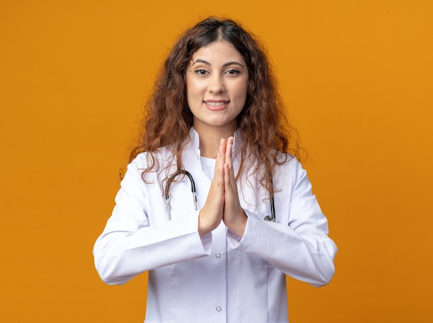 Jovem médica sorridente, vestindo bata médica e estetoscópio olhando para frente, mantendo as mãos no gesto de orar isolado na parede laranja