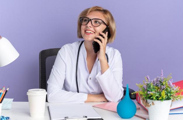 Jovem médica sorridente, vestindo túnica médica com estetoscópio e óculos, se senta à mesa com ferramentas médicas e fala no telefone isolado sobre fundo azul