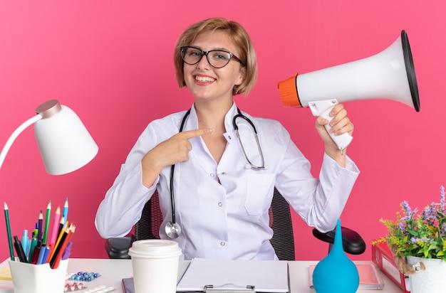 Jovem médica sorridente, vestindo túnica médica com estetoscópio e óculos, sentada na mesa com ferramentas médicas, segurando e aponta para o alto-falante isolado no fundo rosa