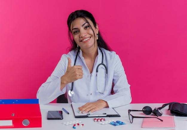 Jovem médica sorridente, vestindo túnica médica e estetoscópio, sentada à mesa com ferramentas médicas, colocando a mão na mesa e aparecendo o polegar isolado na parede rosa