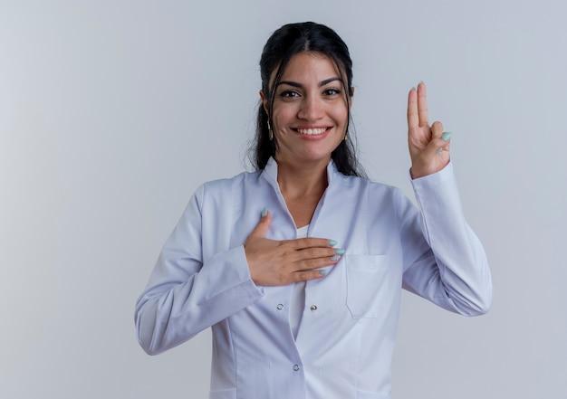 Jovem médica sorridente, vestindo túnica médica, fazendo gesto de promessa isolado na parede branca com espaço de cópia