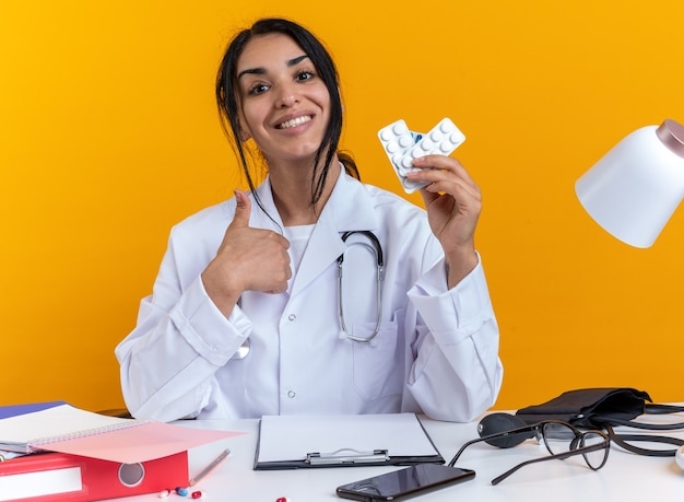 Jovem médica sorridente, vestindo um manto médico com estetoscópio, se senta à mesa com ferramentas médicas segurando comprimidos aparecendo com o polegar isolado no fundo amarelo