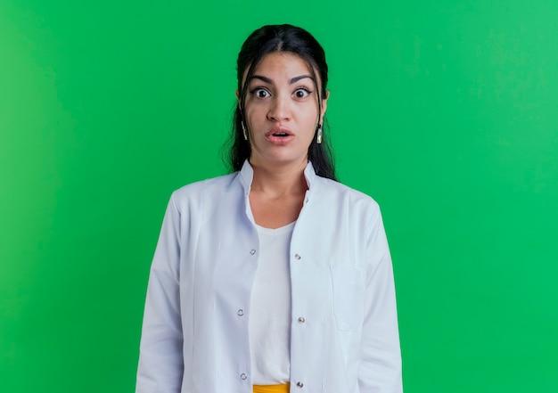 Jovem médica surpreendida usando túnica médica isolada em uma parede verde com espaço de cópia