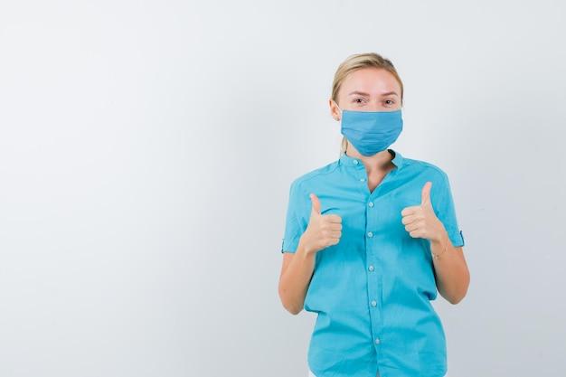 Jovem médica uniformizada mostrando os polegares para cima e parecendo feliz