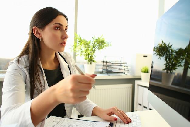 Jovem médica usa computador no local de trabalho