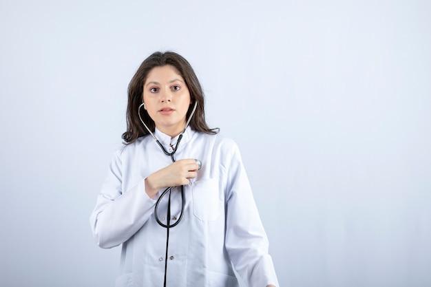 Jovem médica usando estetoscópio para verificar o pulso na parede branca.