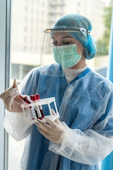 Jovem médica usando protetor facial segurando um tubo de ensaio com uma amostra de sangue com resultado positivo covid-19