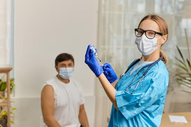 Jovem médica vacina contra o coronavírus covid 19 para um jovem no consultório de uma clínica médica