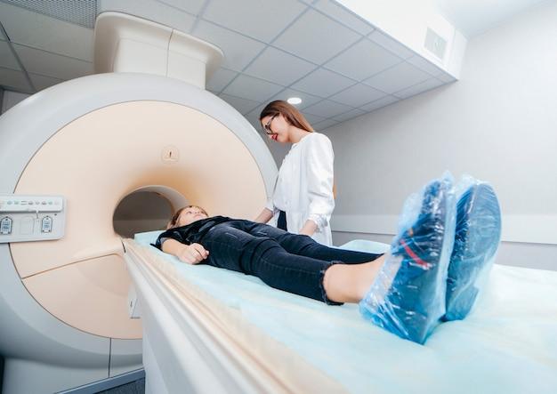 Jovem médica verificando uma criança na sala de ressonância magnética
