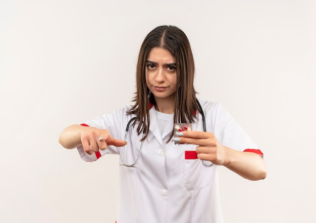 Jovem médica vestindo jaleco branco com estetoscópio em volta do pescoço mostrando bolha com comprimidos apontando com o dedo indicador para frente e rosto sério em pé sobre uma parede branca