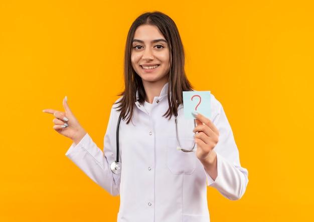Jovem médica vestindo jaleco branco com estetoscópio em volta do pescoço segurando papel lembrete com ponto de interrogação apontando com o dedo para o lado sorrindo olhando para a frente em pé sobre a parede laranja
