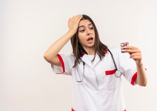 Jovem médica vestindo jaleco branco com estetoscópio em volta do pescoço segurando uma bolha com comprimidos olhando para ela confusa em pé sobre uma parede branca