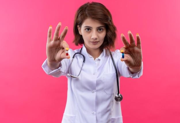 Jovem médica vestindo jaleco branco com estetoscópio mostrando comprimidos nas mãos com rosto sério em pé sobre uma parede rosa