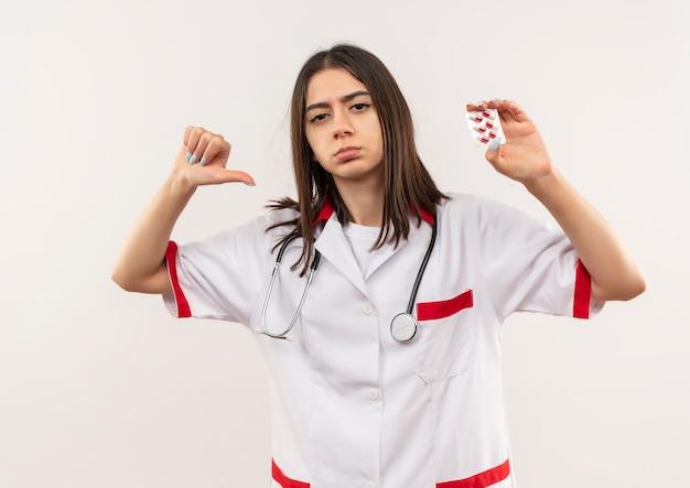 Jovem médica vestindo jaleco branco com estetoscópio no pescoço, mostrando bolha com comprimidos apontando para ela mesma, parecendo satisfeita em pé sobre uma parede branca