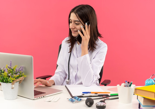 Jovem médica vestindo jaleco branco com estetoscópio no pescoço, trabalhando no computador laptop e falando no celular com um sorriso no rosto, sentada à mesa sobre a parede rosa