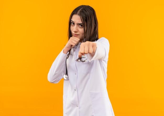Jovem médica vestindo jaleco branco com estetoscópio pendurado no pescoço, olhando para a frente com uma cara séria, posando como uma boxeadora em pé sobre uma parede laranja