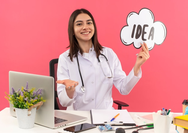 Jovem médica vestindo jaleco branco com estetoscópio pendurado no pescoço, segurando a ideia de sinal de bolha do discurso, sorrindo alegremente sentada à mesa com o laptop sobre a parede rosa