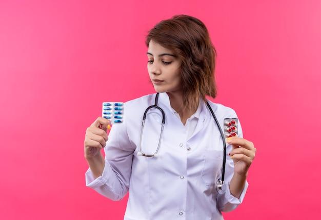 Jovem médica vestindo jaleco branco com estetoscópio segurando uma bolha com comprimidos olhando para ela com cara séria