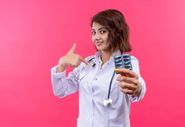 Jovem médica vestindo jaleco branco com estetoscópio segurando uma bolha com comprimidos sorrindo confiante apontando para si mesma