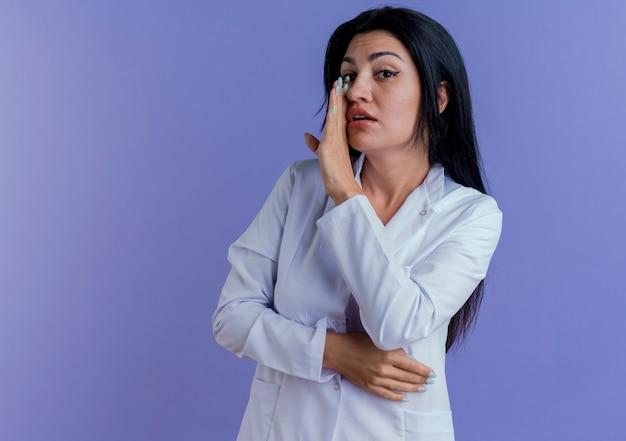 Jovem médica vestindo túnica médica, mantendo a mão perto da boca e sussurrando.
