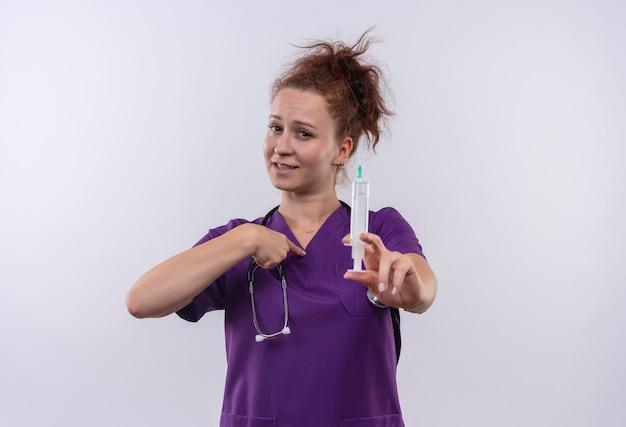 Jovem médica vestindo uniforme médico com estetoscópio segurando uma seringa, sorrindo, apontando com o dedo para si mesma em pé sobre uma parede branca