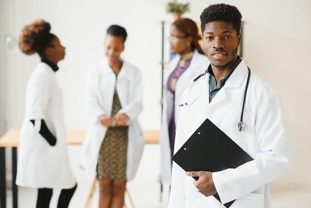 Jovem médico africano do sexo masculino sorrindo em pé no corredor de um hospital com um grupo diversificado de funcionários ao fundo