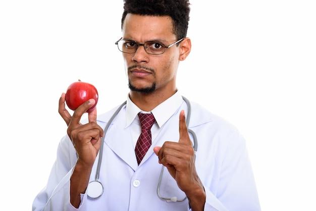 Jovem médico africano segurando uma maçã vermelha enquanto aponta o dedo para cima