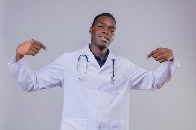 Jovem médico afro-americano satisfeito, vestindo jaleco branco com estetoscópio apontando com o dedo indicador para si mesmo, sorrindo confiante
