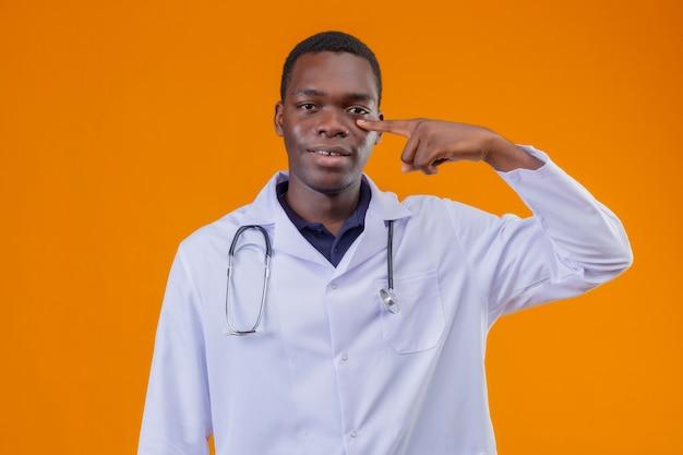 Jovem médico afro-americano vestindo jaleco branco com estetoscópio apontando o dedo para o olho, sorrindo e esperando