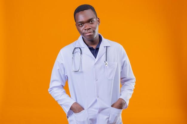 Jovem médico afro-americano vestindo jaleco branco com estetoscópio e as mãos no bolso com expressão confiante e séria no rosto