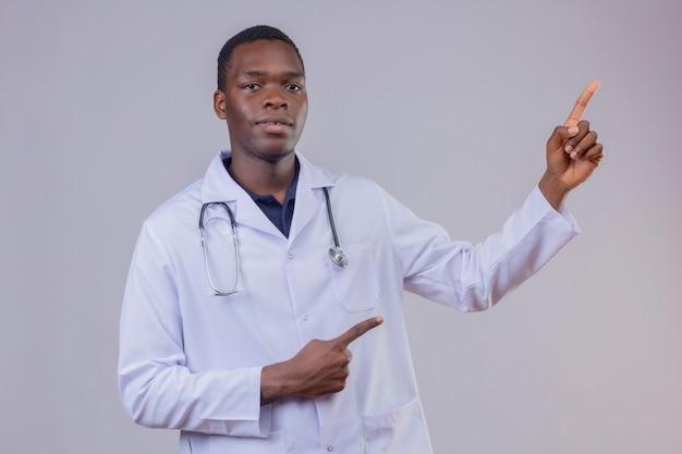 Jovem médico afro-americano, vestindo jaleco branco com estetoscópio, parecendo confiante, apontando com o dedo indicador de ambas as mãos para o lado