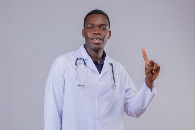 Jovem médico afro-americano vestindo jaleco branco com estetoscópio, parecendo confiante, apontando o dedo indicador para cima