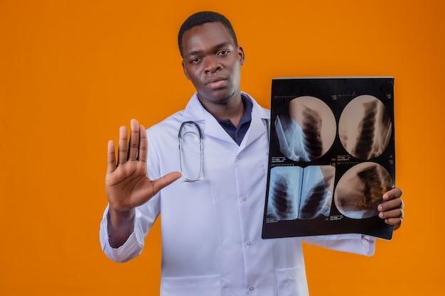 Jovem médico afro-americano vestindo jaleco branco com estetoscópio segurando um raio-x dos pulmões, fazendo sinal de pare com a mão aberta e com cara séria