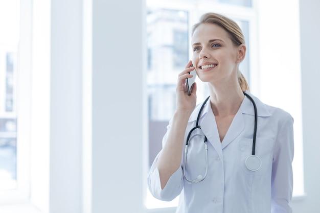 Jovem médico alegre e encantado, desfrutando do horário de trabalho no hospital, enquanto expressa alegria e conversa ao telefone
