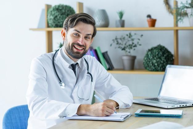Jovem médico alegre fazendo anotações