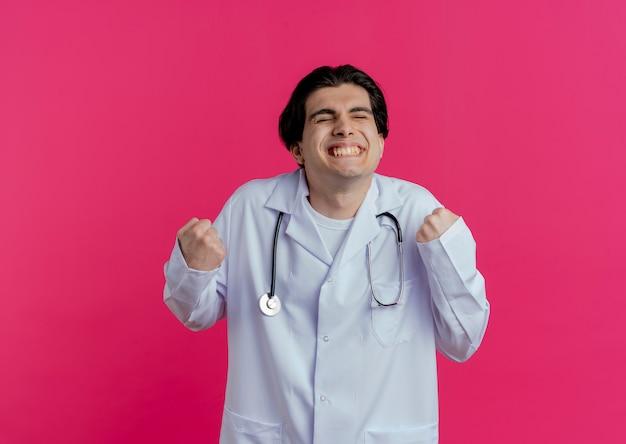 Jovem médico alegre vestindo túnica médica e estetoscópio fazendo gesto de sim com os olhos fechados, isolado na parede rosa com espaço de cópia