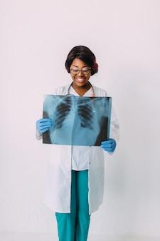 Jovem médico americano africano sorridente em roupas médicas, segurando o raio-x do paciente
