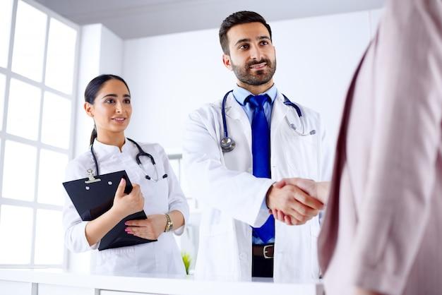 Jovem médico árabe agita as mãos com um paciente em um hospital