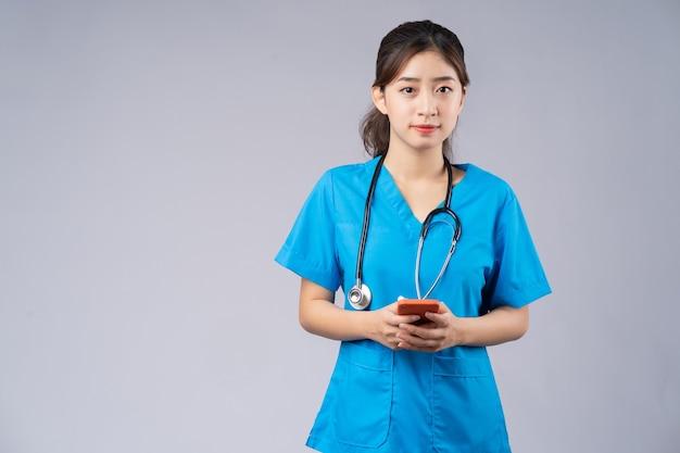 Jovem médico asiático com smartphone cinza