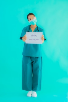 Jovem médico asiático usar máscara mostrar social distanciamento na placa de papel