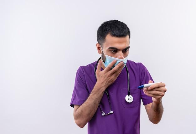 Jovem médico assustado vestindo roupas roxas de cirurgião e máscara médica de estetoscópio olhando para o termômetro em sua mão, cobrindo a boca com a mão em um fundo branco isolado