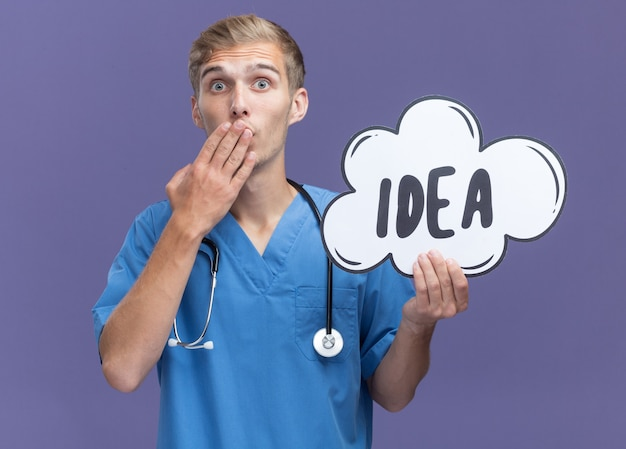 Jovem médico assustado vestindo uniforme de médico com estetoscópio segurando uma bolha de ideia, boca coberta com a mão isolada na parede azul