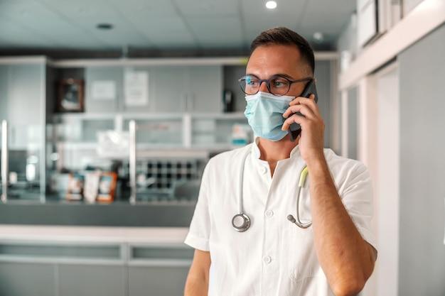 Jovem médico atraente com máscara facial, usando telefone inteligente para chamadas de emergência.